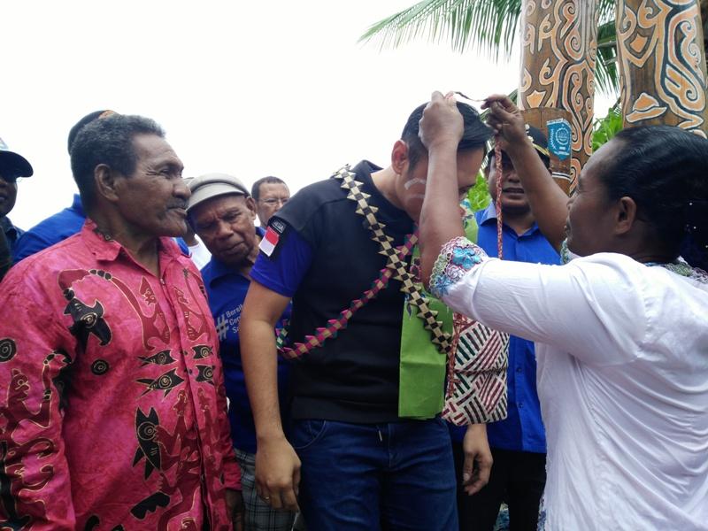 Masyarakat Kampung Arborek mengalungkan tas noken sebagai ucapan selamat datang di Kampung Arborek