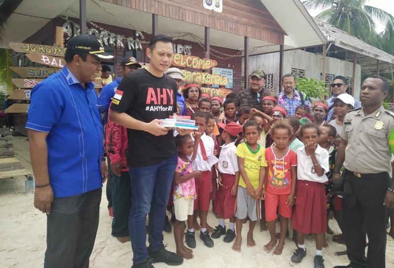 Pemberian bantuan buku bacaan secara simbolis oleh AHY didampingi Ketua DPC Partai Demokrat Raja Ampat kepada siswa SD Arborek