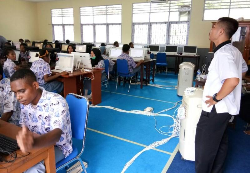 Seorang guru tengah memantau para murid yang sedang praktek komputer