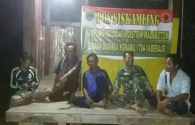 Satgas TMMD bersama masyarakat melakukan penjagaan di Pos Kamling