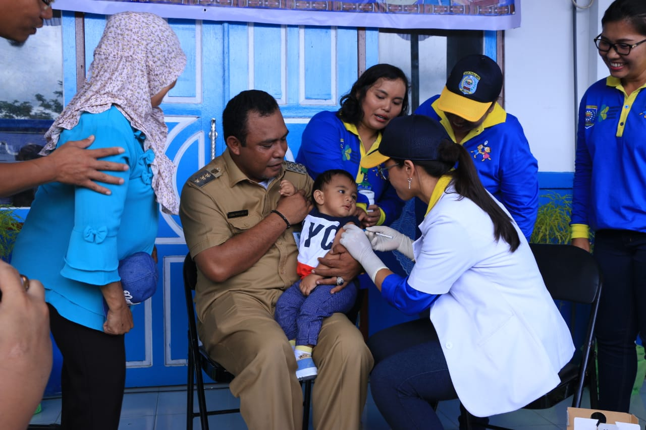 Abdul Faris Umlati, Bupati Raja Ampat saat memberikan imunisasi kepada anak kandungnya